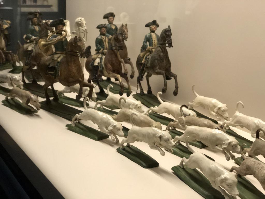 Reitende Jäger einer Parforcejagd folgen ihren Jagdhunden. Gesprächsstoff zum Dessert im Bayerischen Nationalmuseum